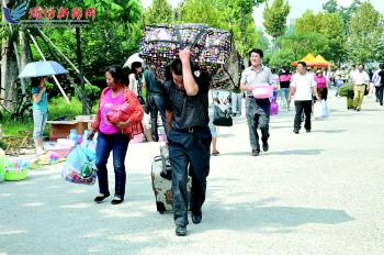 潍坊医学院校园内 一位新生家长被沉重的行李压弯了腰