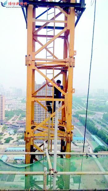 一名塔吊工正顺着塔吊往下爬